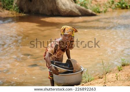 BANDIAGARA, MALI, AFRICA - AUGUST, 28, 2011 Girl doing heavy work tasks in the river