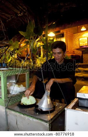 BANDUNG-JUNE 26 : Bapak Omon prepares Kue Ape a traditional dessert for tourist at Kampung Daun Culture Gallery & Cafe on June 26, 2011 in Bandung, Indonesia.Bandung economy is built on tourism.