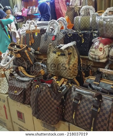 BANDUNG, WEST JAVA ISLAND, INDONESIA -SEPTEMBER 16, 2014: Large collection of famous fake handbags on display at one of the shopping centres in Bandung. The fake handbags are widely sold cheaply here. #218037019