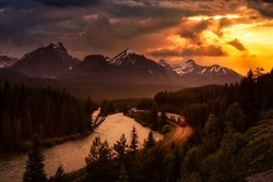 Banff National Park, Alberta, Canada. Iconic View of Morant's Curve with Canadian Rocky Mountains in the background and Train Riding by the river. Dramatic Sunset Art Render