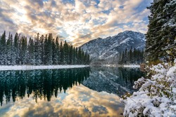 Banff National Park beautiful natural scenery in winter sunset time. Mount Norquay with colourful clouds reflected on Bow River like a mirror. Town of Banff, Canadian Rockies.