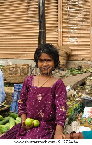BANGALORE, INDIA - JUNE 26: An unidentified vendor girl sells fruit on an unnamed street in Bangalore, India on June 26, 2011. About 42 percent of India falls below the international poverty line of $1.25 a day.