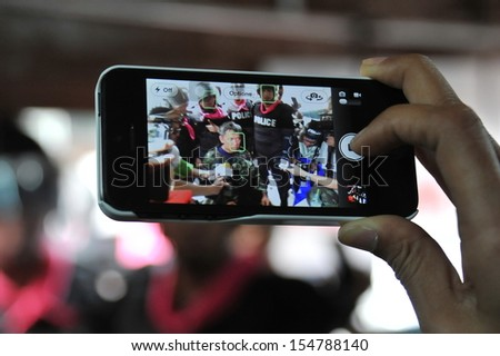 BANGKOK - AUG 7: A journalist uses a smartphone to capture an interview of activist Capt Songklod Chuenchupol after his arrest during an anti-amnesty bill rally on Aug 7, 2013 in Bangkok, Thailand.