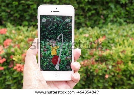 BANGKOK - AUG 6, 2016 : Apple iPhone5 held in one hand showing its screen with Pokemon Go application, catching Pikachu, electrical-typed electrical Pokemon. This app is worldwide hit after its launch #464354849