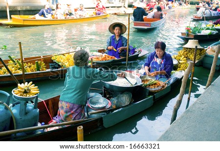 BANGKOK - AUGUST 2008: Damnoean Saduak floating market, Bangkok Thailand, Aug 2008. Local women selling fried bananas on wooden boats. Old and traditional way of selling and buying food and fresh produce. August 2008.