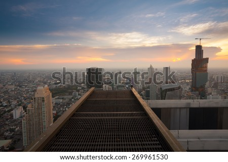 Bangkok city sunset view from rooftop of skyscraper building with steel grate floor