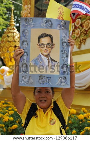 BANGKOK - DEC 5 : A woman holds a portrait of Thai King Bhumibol Adulyadej after attending celebrations of the King's 85th birthday held on the Royal Plaza on Dec 5, 2012 in Bangkok, Thailand.