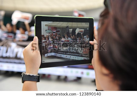 BANGKOK - DEC 9: An passer-by uses an iPad tablet to photograph protesters on Thai Anti-Corruption Day organised by the United Nations Development Programme on Dec 9, 2012 in Bangkok, Thailand.