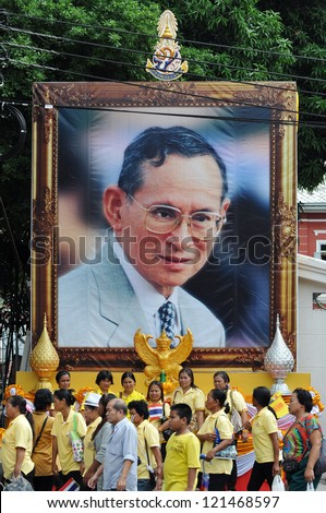 BANGKOK - DEC 5: Royalists walk past a large portrait of Thai King Bhumibol Adulyadej after attending celebrations of the King's 85th birthday on the Royal Plaza on Dec 5, 2012 in Bangkok, Thailand.