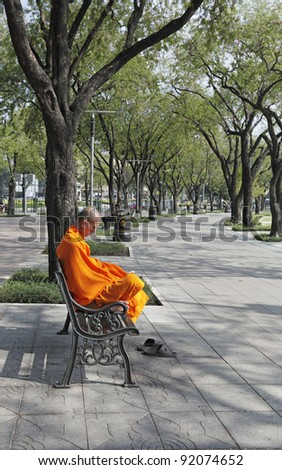 BANGKOK - DECEMBER 25: A monk meditating in a park on December 25, 2011 in Sanam Luang Park, Bangkok. Buddhist monk received alms every year end in Sanam Luang Park before embarking on a 3 month fast.