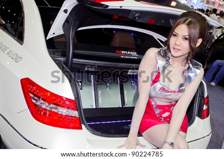 BANGKOK - DECEMBER 4: Female presenters model at the Nissan Teana car audio booth at the 28th Thailand International Motor Expo on December 4, 2011 in Bangkok, Thailand. - stock photo