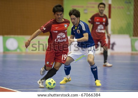 BANGKOK - DECEMBER 12 : Thailand vs Japan Bangkok Futsal Super Match 2010.Kohei Harada (Blue) and Thananchai Chomboon(Red) on DECEMBER 11 -12 2010 in Bangkok Thailand. - stock photo