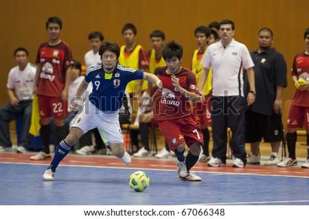 BANGKOK - DECEMBER 12 : Thailand vs Japan Bangkok Futsal Super Match 2010.Tomoaki Watanabe (Blue) and Kritsada Wongkaeo(Red) on DECEMBER 11 -12 2010 in Bangkok Thailand.