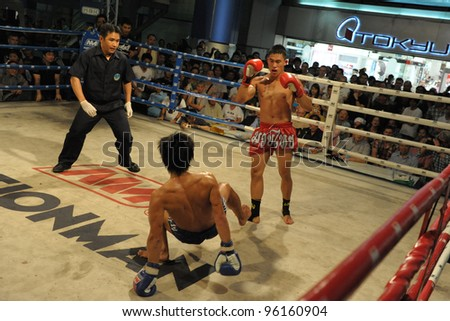 BANGKOK - FEB 22: An unidentified Muay Thai fighter is knocked to the mat during a Thai kickboxing match at MBK Fight Night on Feb 22, 2012 in Bangkok, Thailand. - stock photo