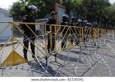 BANGKOK - FEB 11:  Riot police  guard a barricade outside Government House during a yellow-shirt protest on Jan 25, 2011 in Bangkok, Thailand. The Thai capital continues to see street protests. - stock photo