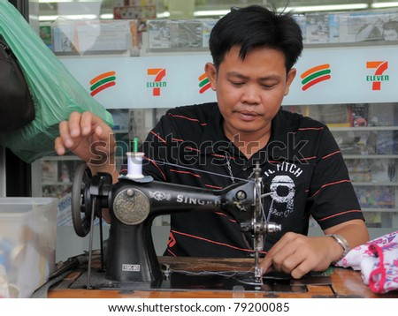 BANGKOK - FEB 1: Unidentified man operates a sewing machine in a garments shop on Feb 1, 2011 in Bangkok, Thailand. Textile and clothing is Thailand's largest manufacturing industry.