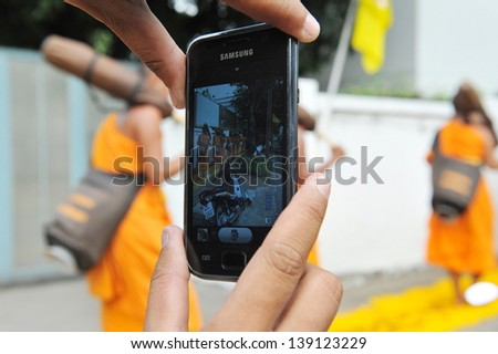 BANGKOK - JAN 25: A smartphone user captures a Buddhist monks on a pilgrimage in central Bangkok on Jan 25, 2013 in Bangkok, Thailand. Thousands gathered along the route to watch the pilgrimage.