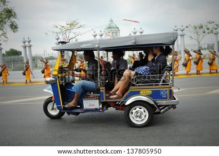 BANGKOK - JAN 25: A tuk tuk taxi transports passengers on a road in Dusit district on Jan 25, 2013 in Bangkok, Thailand. Tuk tuks can be hired from as little as $1 or B30 a fare for shop trips.