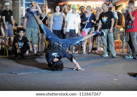 BANGKOK - JAN 3: An unidentified b-boy breakdances at an informal street dance meet on Jan 3, 2011 in Bangkok, Thailand. Breakdancing is a popular activity of youth in the Thai capital.