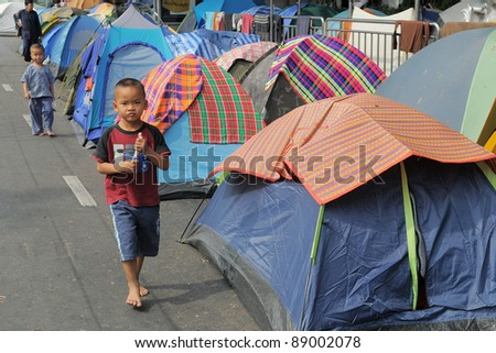 BANGKOK - JAN 20: An unidentified boy walks through a roadside tent village outside Government House during a large yellow-shirt anti-government protest on 20, 2011 in Bangkok, Thailand.