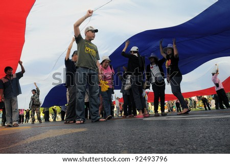 BANGKOK - JAN 25: Nationalist yellow-shirt protesters under a Thai flag near Government House during a large anti-government rally on Jan 25, 2011 in Bangkok, Thailand.