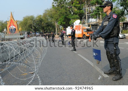 BANGKOK - JAN 25: Riot police behind razor wire guard Government House as yellow-shirt protesters hold a large rally Jan 25, 2011 in Bangkok, Thailand.
