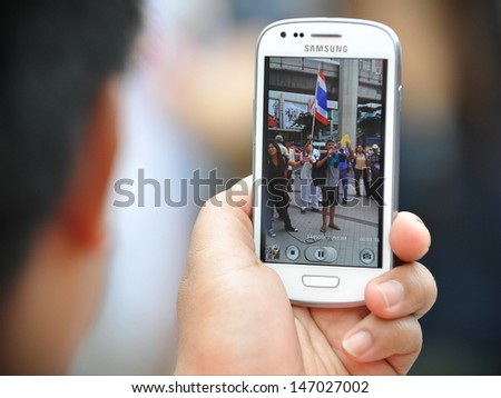 BANGKOK JULY 21 A protester uses a smartphone to video an anti-government rally on July 21 2013 in Bangkok Thailand The protesters are calling for the government to be overthrown