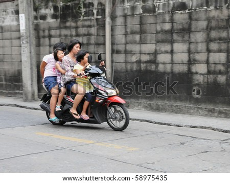 BANGKOK - JUNE 9: Unidentified family on a motorbike in the Thai capital June 9, 2010 in Bangkok, Thailand. The use of motorbikes as family transport is commonplace throughout much of Southeast Asia.