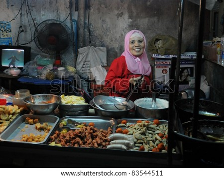 BANGKOK - JUNE 19: Unidentified street vendor cooks at a roadside restaurant June 19, 2011 in Bangkok, Thailand. There are more than 16,000 registered street vendors in Bangkok.