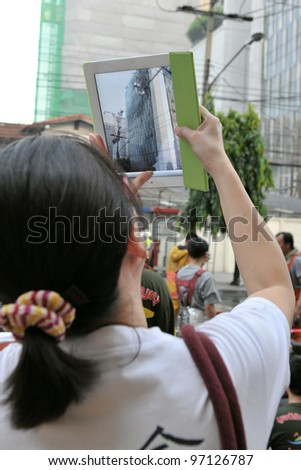 BANGKOK - MAR 5: An unidentified passer by uses a tablet computer to photograph firefighters tackling a blaze at Fico Building on Asoke Road in the city centre on Mar 5, 2012 in Bangkok, Thailand.