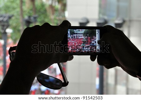 BANGKOK - MAY 19: A passerby photographs a red-shirt rally at Ratchaprasong on May 19, 2011 in Bangkok, Thailand. The protesters gathered to mark a year since 91 people died in clashes in Bangkok.