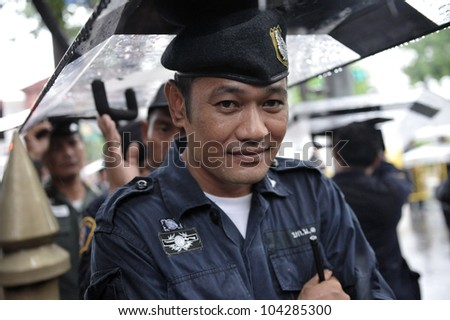 BANGKOK - MAY 31: A policeman uses a riot shield to shelter from rain during People's Alliance for Democracy, or yellow-shirt, rally outside Parliament on May 31, 2012 in Bangkok, Thailand.