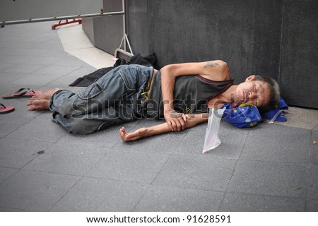 BANGKOK - MAY 19: An unidentified man sleeps on the street in city centre on May 19, 2011 in Bangkok, Thailand. The government estimates 4,000 homeless in Bangkok while NGOs put the figure far higher.