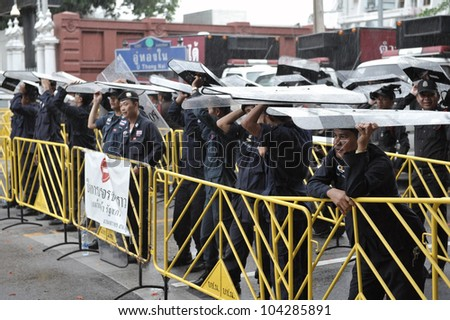 BANGKOK - MAY 31: Policemen stand guard at a barricade during an anti-government People's Alliance for Democracy, or yellow-shirt, rally outside Parliament on May 31, 2012 in Bangkok, Thailand.