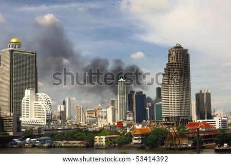 BANGKOK - MAY 19 : Smoke billow as red-shirt protesters set fire on tires May 19, 2010 in Bangkok.The government armored personnel carriers smash red-shirt protesters barricades and enter Lumpini park