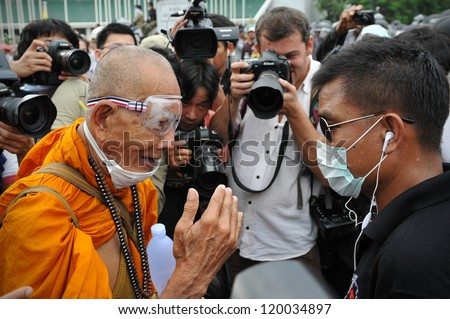 BANGKOK - NOV 24: A Buddhist monk talks with a Nationalist anti-government protester from Pitak Siam at a rally on Makhawan Bridge on Nov 24, 2012 in Bangkok, Thailand.