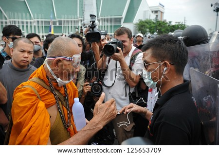 BANGKOK - NOV 24: A Buddhist monk talks with a Nationalist protester from Pitak Siam at a police roadblock on Makhawan Bridge during a large anti-government rally on Nov 24, 2012 in Bangkok, Thailand.