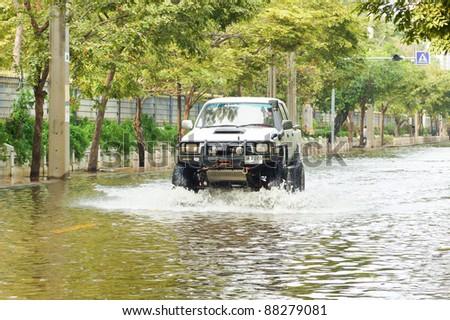 BANGKOK - NOV 05, 2011: A car drives through flooded Kampangpeth 3 Rd between Jatujak park and Wachirabenchatat Park, in  Capital center on Nov 05, 2011 in Bangkok, Thailand.