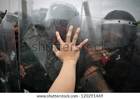BANGKOK - NOV 24: A protester from the nationalist Pitak Siam group pushes the shield of riot police during a violent anti-government rally with riot police on Nov 24, 2012 in Bangkok, Thailand.