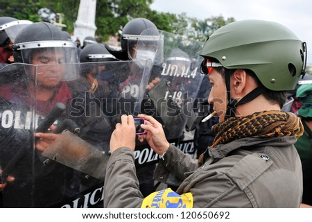 BANGKOK - NOV 24: A protesters uses a smartphone to photograph riot police while participating in an anti-government rally organised by nationalist Pitak Siam on Nov 24, 2012 in Bangkok, Thailand.