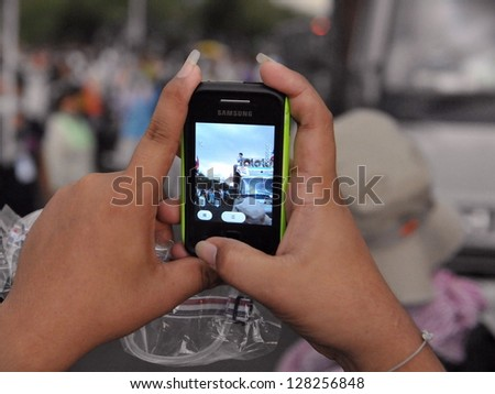 BANGKOK - NOV 24: A protesters uses a smartphone to video an anti-government Pitak Siam rally at Makhawan Bridge on Nov 24, 2012 in Bangkok, Thailand. An estimated 20,000 protesters joined the rally.