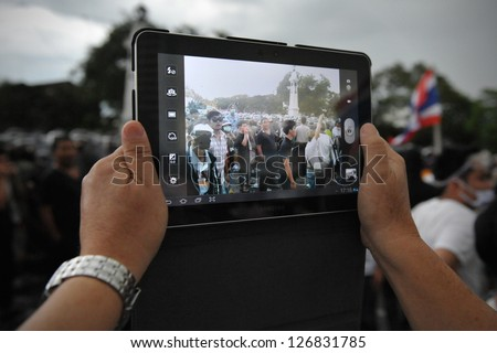 BANGKOK - NOV 24: A protesters uses a tablet computer to photograph an anti-government rally organised by the nationalist Pitak Siam group on Nov 24, 2012 in Bangkok, Thailand.