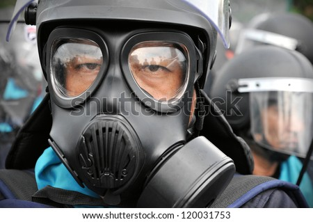 BANGKOK - NOV 24: A riot police officer wears a gas mask at anti-government rally at Makhawan Bridge on Nov 24, 2012 in Bangkok, Thailand. Police fired tear gas to deter protesters.