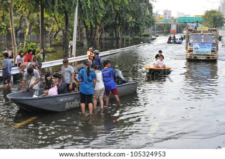 BANGKOK - NOV 4: Boats and trucks navigates a flooded road in Pinklao district in rescuing flood victims as Thailand faces its worst flooding in 50 years on Nov 4, 2011 in Bangkok, Thailand.