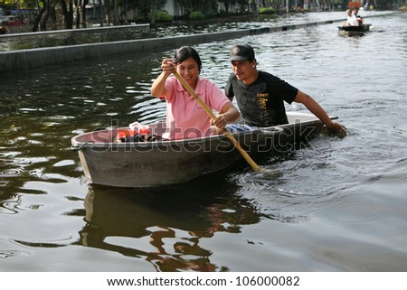 BANGKOK - NOV 4: City residents row through a flooded street as tens of thousands evacuate their homes in the worst flooding in over 50 years on Nov 4, 2011 in Bangkok, Thailand. - stock photo
