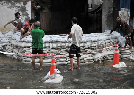 BANGKOK - OCT 26: Residents of Bangkok's Dusit district man a flood barrier as the city faces its worst flooding in over 50 years on Oct 26, 2011 in Bangkok, Thailand.