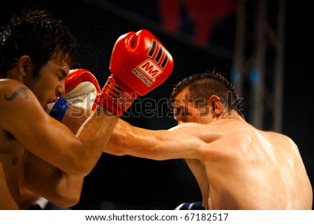 BANGKOK - OCTOBER 12: A solid left jab from a muay thai fighter sends sweat flying from the head of his opponent at Fight Night October 12, 2010 at Bangkok, Thailand