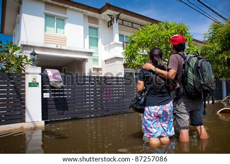 BANGKOK - OCTOBER 24: An unidentified couple looks at their flooded house on of October 24, 2011 in Bangkok, Thailand. The area is flooded due to recent monsoons.
