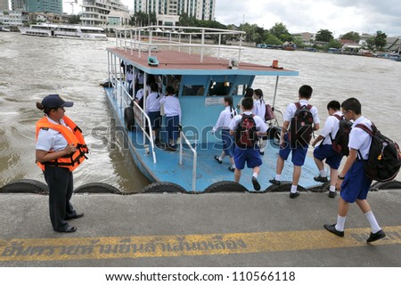 BANGKOK - SEP 14: School children board a ferry on Chao Phraya River on Sep 14, 2011 in Bangkok, Thailand. The Chao Phraya is on flood alert as rain run-off from upcountry reaches the Thai capital.