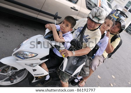 BANGKOK - SEPT 12: Unidentified family make a school run by motorbike during evening rush hour on Sept 12, 2011 in Bangkok, Thailand. The use of motorbikes as family transport is commonplace in Thailand.
